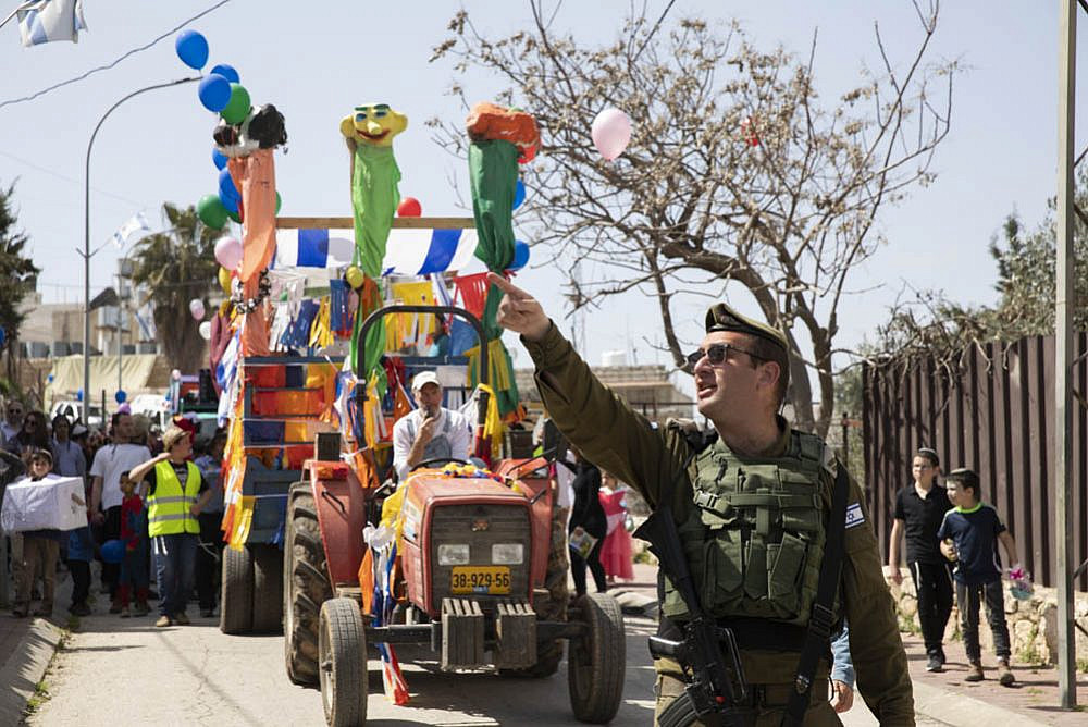 An Israeli soldier seen during the annual Purim parade in Hebron's city center, West Bank, March 10, 2020. (Oren Ziv)