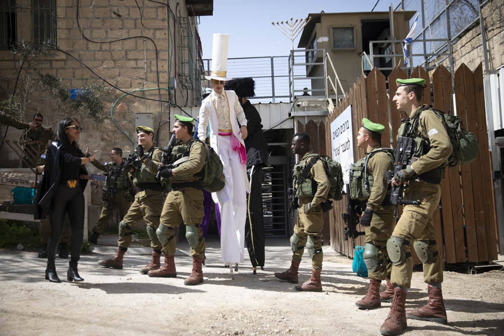 Israeli soldiers watch on as Hebron's settlers hold their annual Purim parade in the city, March 10, 2020. (Oren Ziv)