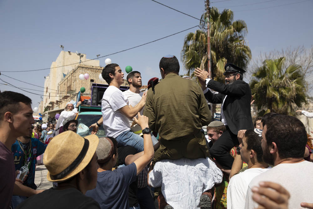 Israeli settlers dance with an IDF commander during the annual Purim parade in occupied Hebron, West Bank, March 10, 2020. (Oren Ziv)