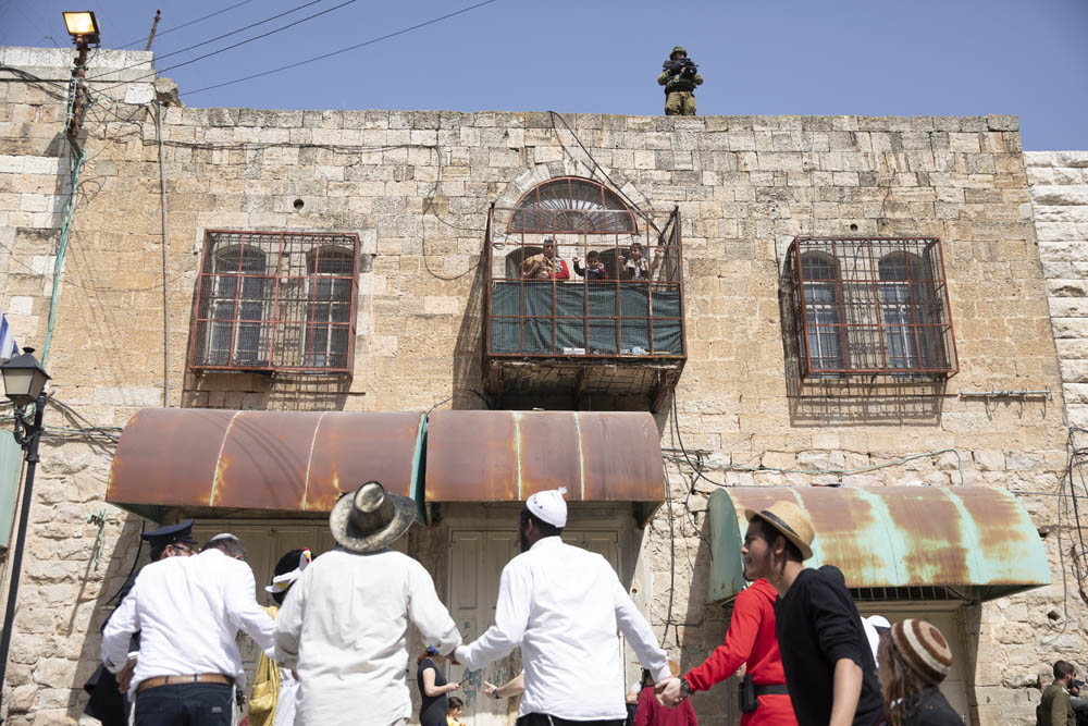 Israeli settlers dance during the annual Purim parade in the West Bank city of Hebron. Palestinians, who were forbidden from leaving their homes during the march, can be seen looking on from their balcony, March 10, 2020. (Oren Ziv)