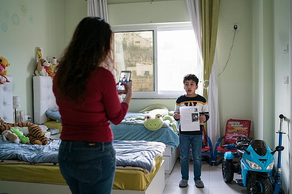 Carol Janine takes a video of her son Milan at their home in Bethlehem as he recites his homework, to send it to his teacher on March 11, 2020. (Samar Hazboun)