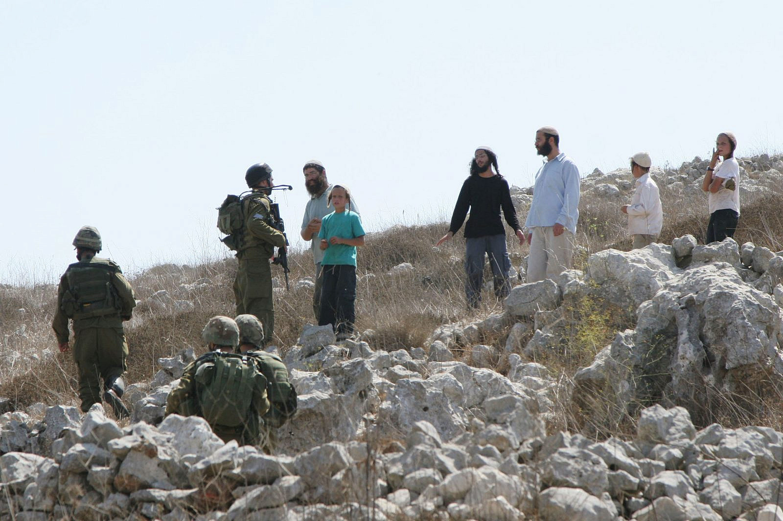 Jewish settlers argue with Israeli soldiers during a confrontation between the settlers and Palestinians over farming land between the Jewish settlement of Bracha and the West Bank village of Burin on September 21, 2010. (Wagdi Ashtiyeh/Flash90)