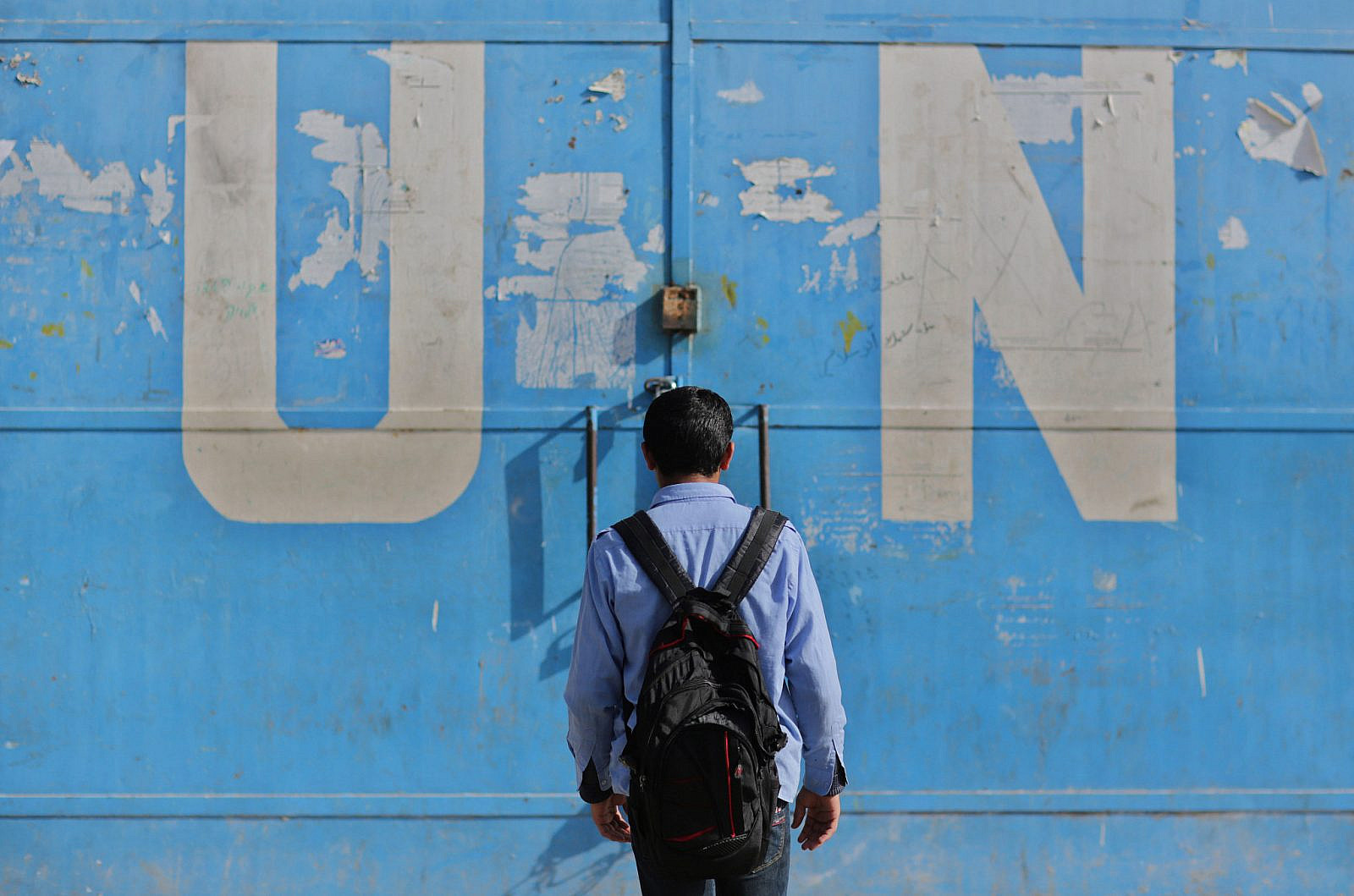 Palestinian students walk past a UN distribution center in the Jabalia refugee camp in the northern Gaza Strip on April 6, 2013. (Wissam Nassar/FLASH90)