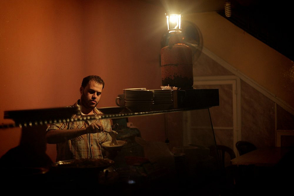 A Palestinian uses a gas lighter while working inside his restaurant during a power cut in Gaza Strip, November 17, 2013. (Emad Nassar/Flash90)