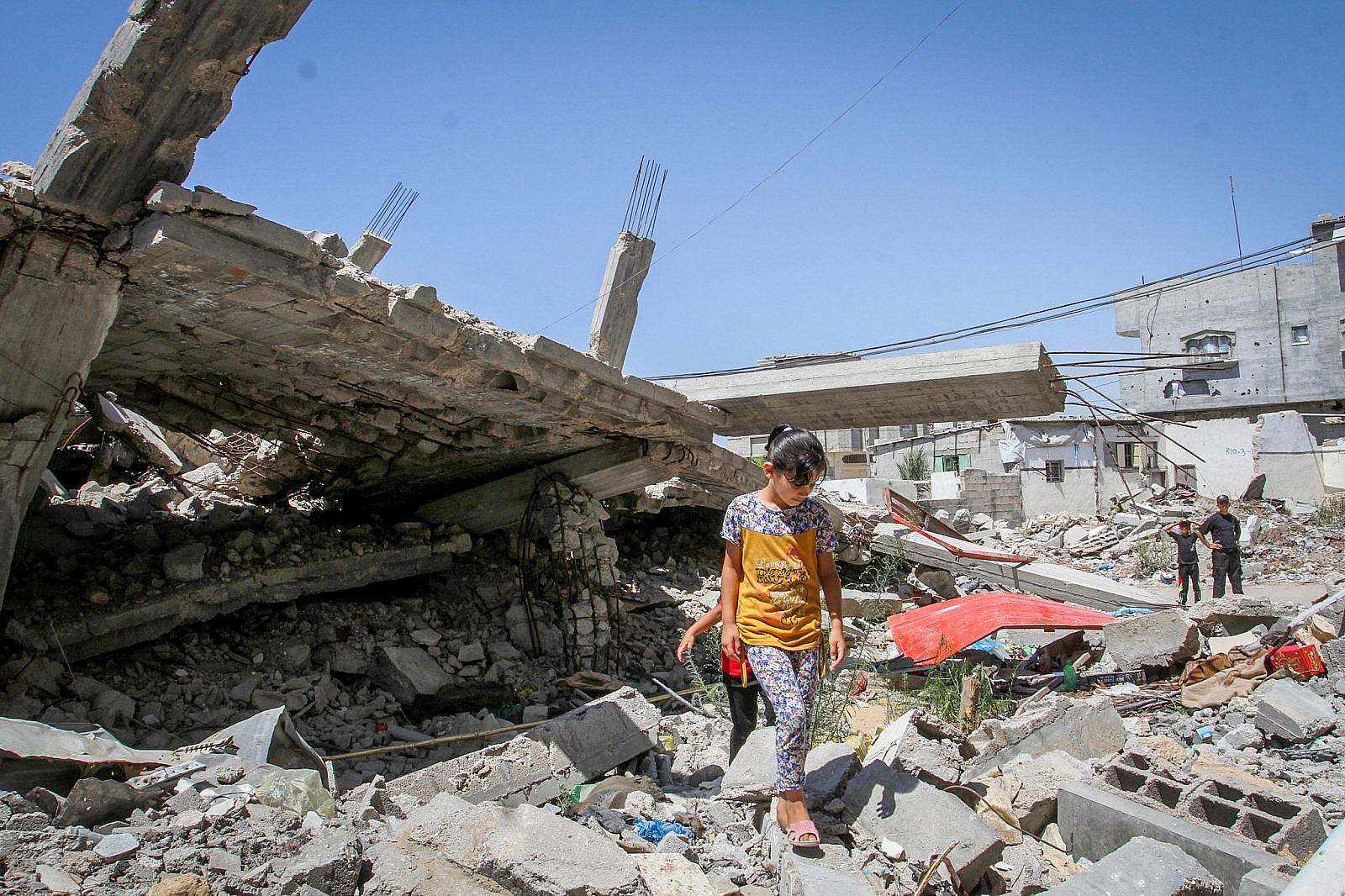 Palestinian girls play in the rubble of a house, which was destroyed during the 50-day war between Israel and Hamas in the summer of 2014, in Rafah in the southern Gaza Strip on July 30, 2015. (Abed Rahim Khatib/Flash 90)