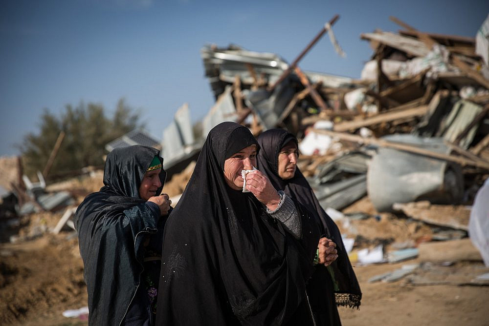 Bedouin women collect their belongings from the ruins of their demolished homes in the unrecognized village of Umm al-Hiran in the Negev desert, in the in the Southern Israel, January 18, 2017. (Hadas Parush/Flash90)