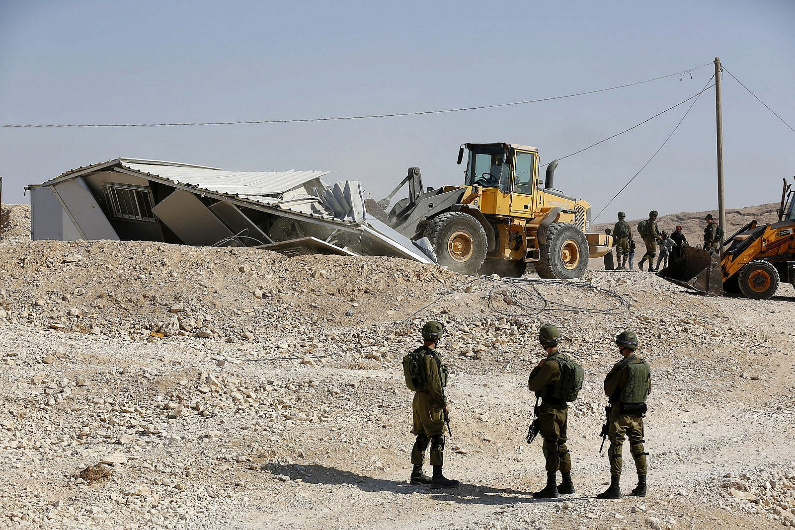 Israeli soldiers stand guard during the demolishing of caravans that were donated by the European Union in the West Bank village of Khashim Al-Daraj, near Yatta, August 14, 2017. (Wisam Hashlamoun/Flash90)