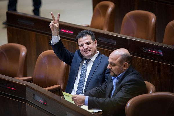 Joint List chairperson Ayman Odeh waves the 'V' sign for victory during a plenum session in the assembly hall of the Israeli parliament, on November 13, 2017. (Yonatan Sindel/Flash90)