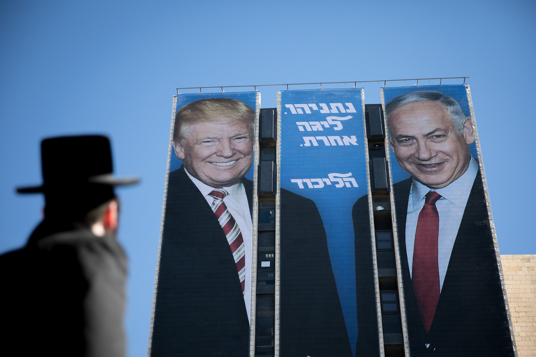 An ultra-Orthodox Jewish man looks at a large billboard of U.S. President Donald Trump and Israeli Prime Minister Benjamin Netanyahu, as part of the Likud election campaign, at the entrance to Jerusalem, Feb. 3, 2019. (Yonatan Sindel/Flash90)