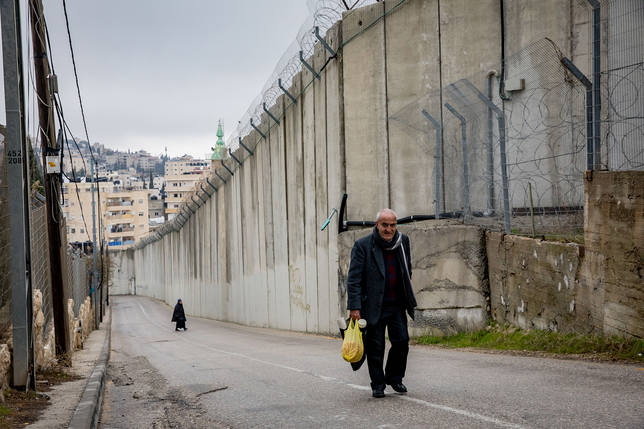 Palestinians walk past a section of the separation wall in the East Jerusalem village of Abu Dis, February 02, 2020. (Olivier Fitoussi/Flash90)