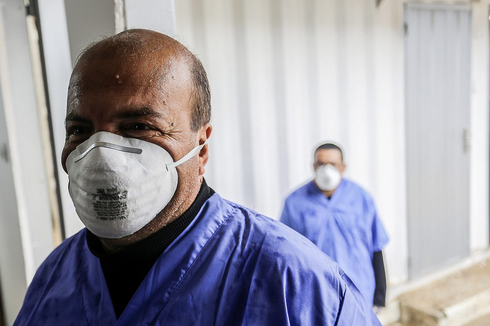 Palestinian workers wearing protective masks as they prepare the quarantine zone to test returning passengers for coronavirus, at Rafah border crossing in the Gaza Strip, February 16, 2020. (Abed Rahim Khatib/Flash90)