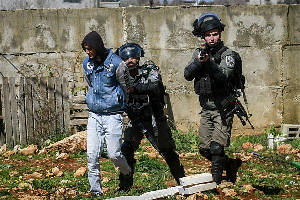 Israeli security forces arrest a Palestinian man as Israeli bulldozers operate on land near the West Bank city of Nablus, March 1, 2020. (Nasser Ishtayeh/Flash90)