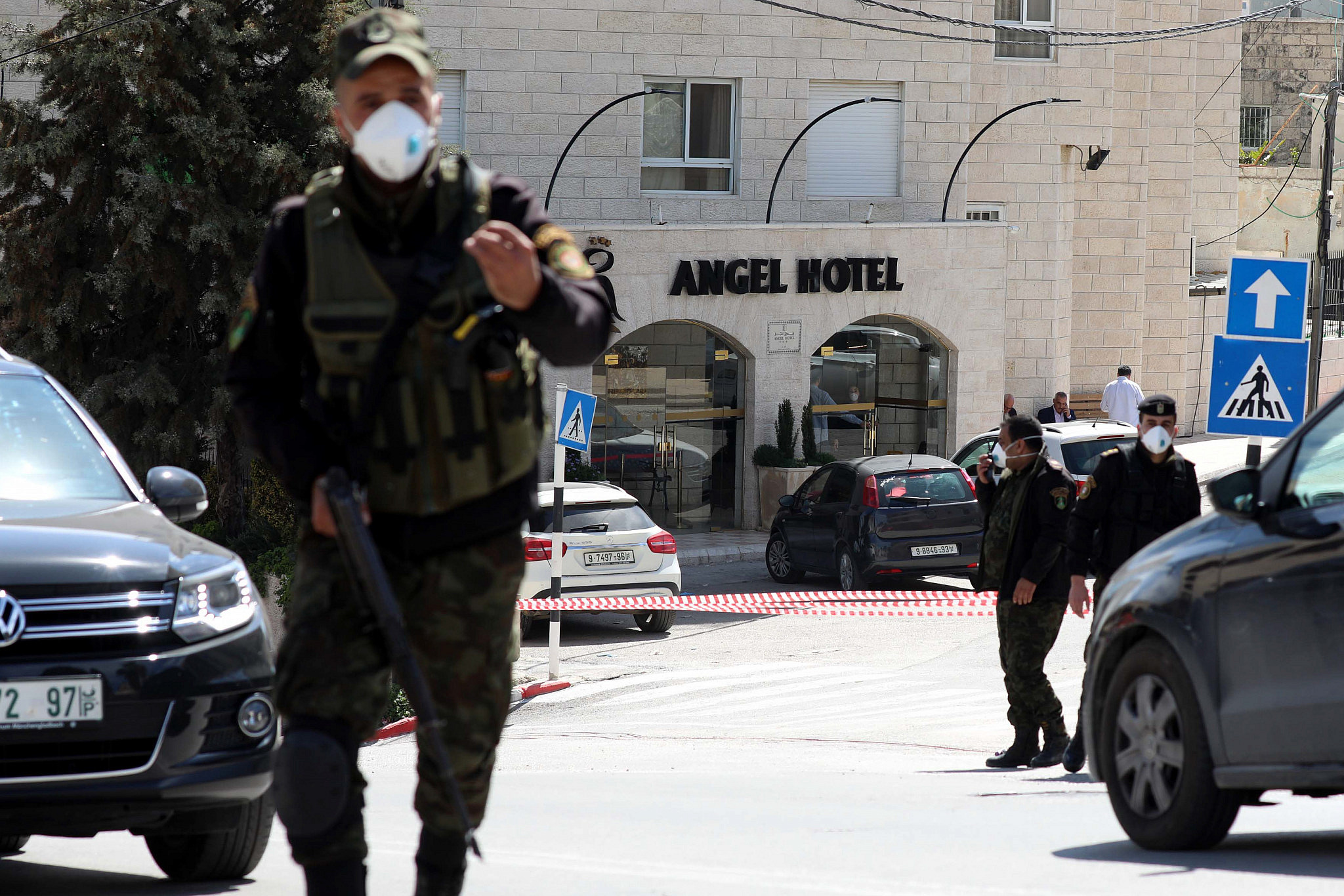 Palestinian security forces wearing face masks block the entrance to the Angel Hotel in Beit Jala town, near Bethlehem, March 5, 2020. (Wissam Hashlamoun/Flash90.)
