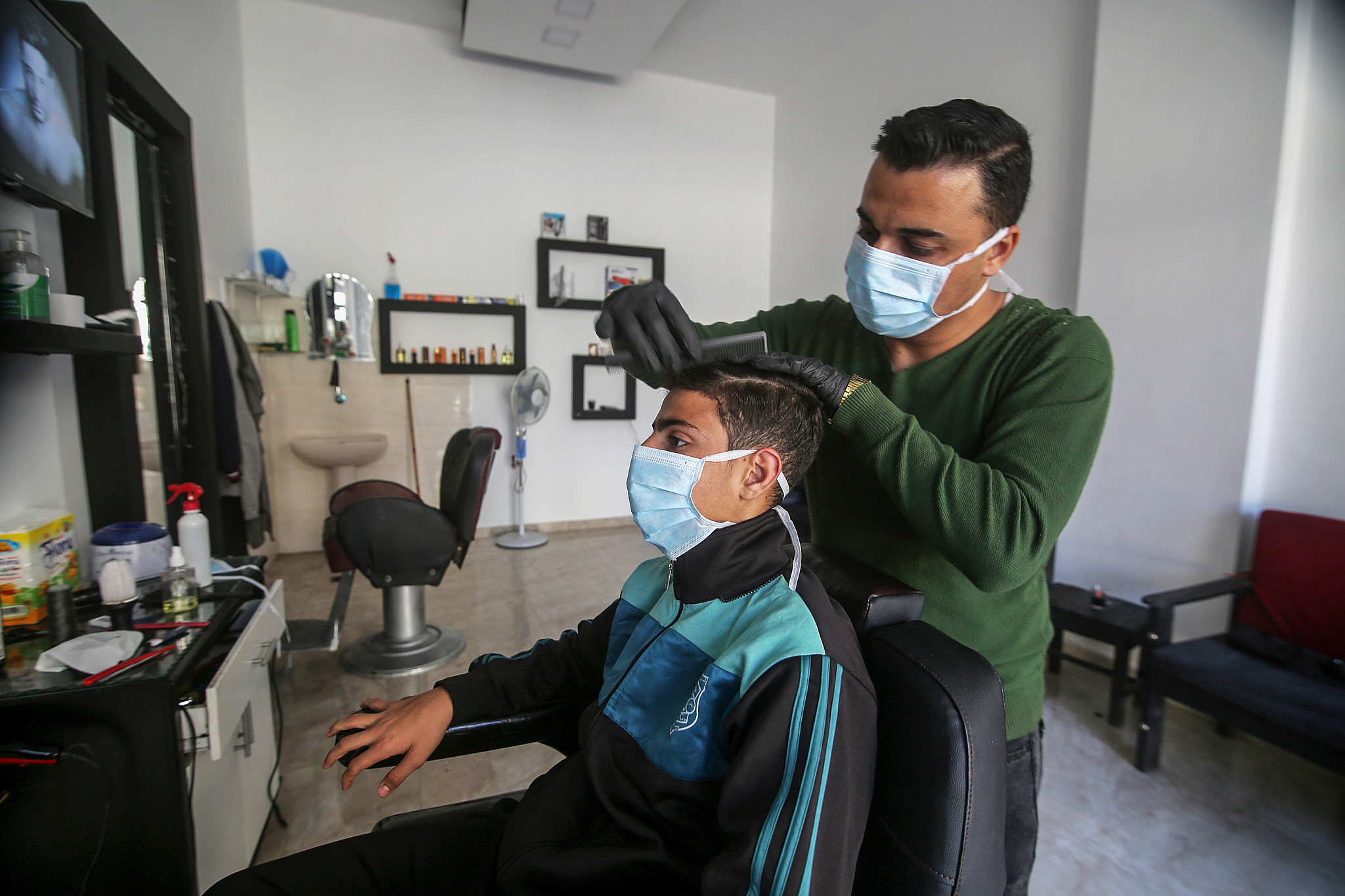 Palestinians wear face masks for fear of the coronavirus at a barbershop in Khan Yunis, southern Gaza Strip, on March 7, 2020. (Abed Rahim Khatib/Flash90)