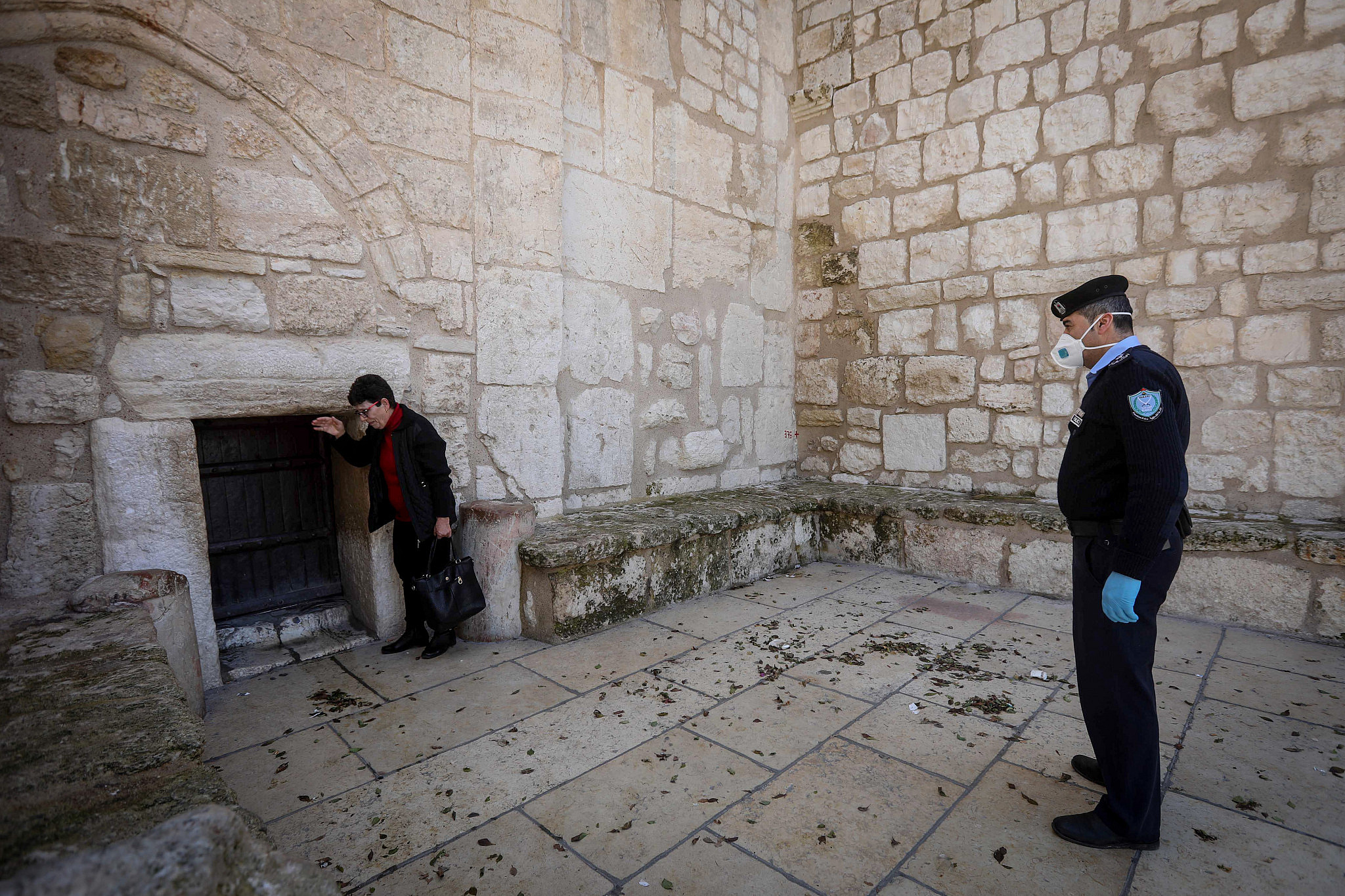 A Palestinian police officer wears a mask to protect himself from the coronavirus, outside the closed Church of the Nativity in the West Bank city of Bethlehem, March 8, 2020. (Wisam Hashlamoun/Flash90)