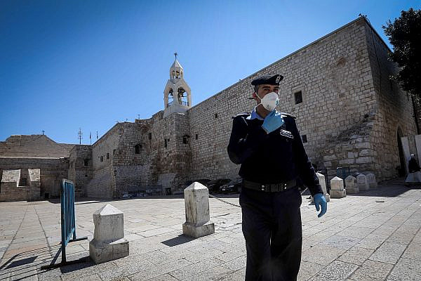 A Palestinian police officer wears a mask to protect himself from coronavirus stands outside the closed Church of the Nativity in the West Bank city of Bethlehem, March 8, 2020. (Wisam Hashlamoun/Flash90)