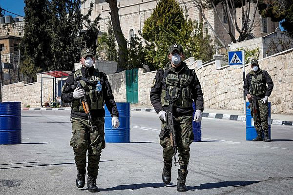 Palestinian security forces wearing face masks block the entrance to the West Bank city of Bethlehem, March 8, 2020. (Wisam Hashlamoun/Flash90)
