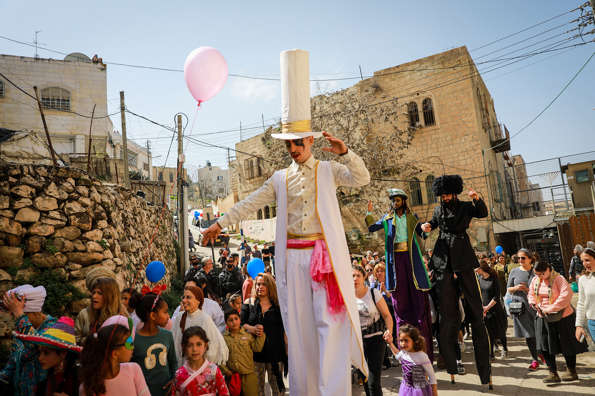 Jewish settlers wearing costumes take part in the annual parade marking the Jewish holiday of Purim in the occupied West Bank city of Hebron, March 10, 2020. (Yonatan Sindel/Flash90)