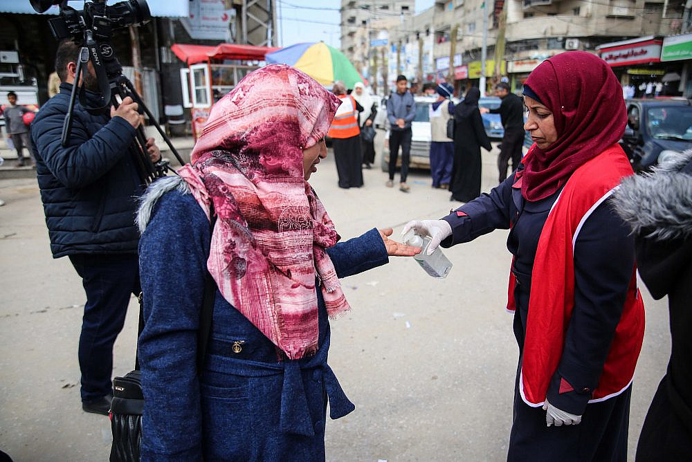 Palestinian health workers give passersby hand sanitizer in Gaza City as a precaution from COVID-19, March 15, 2020. (Ali Ahmed/Flash90)