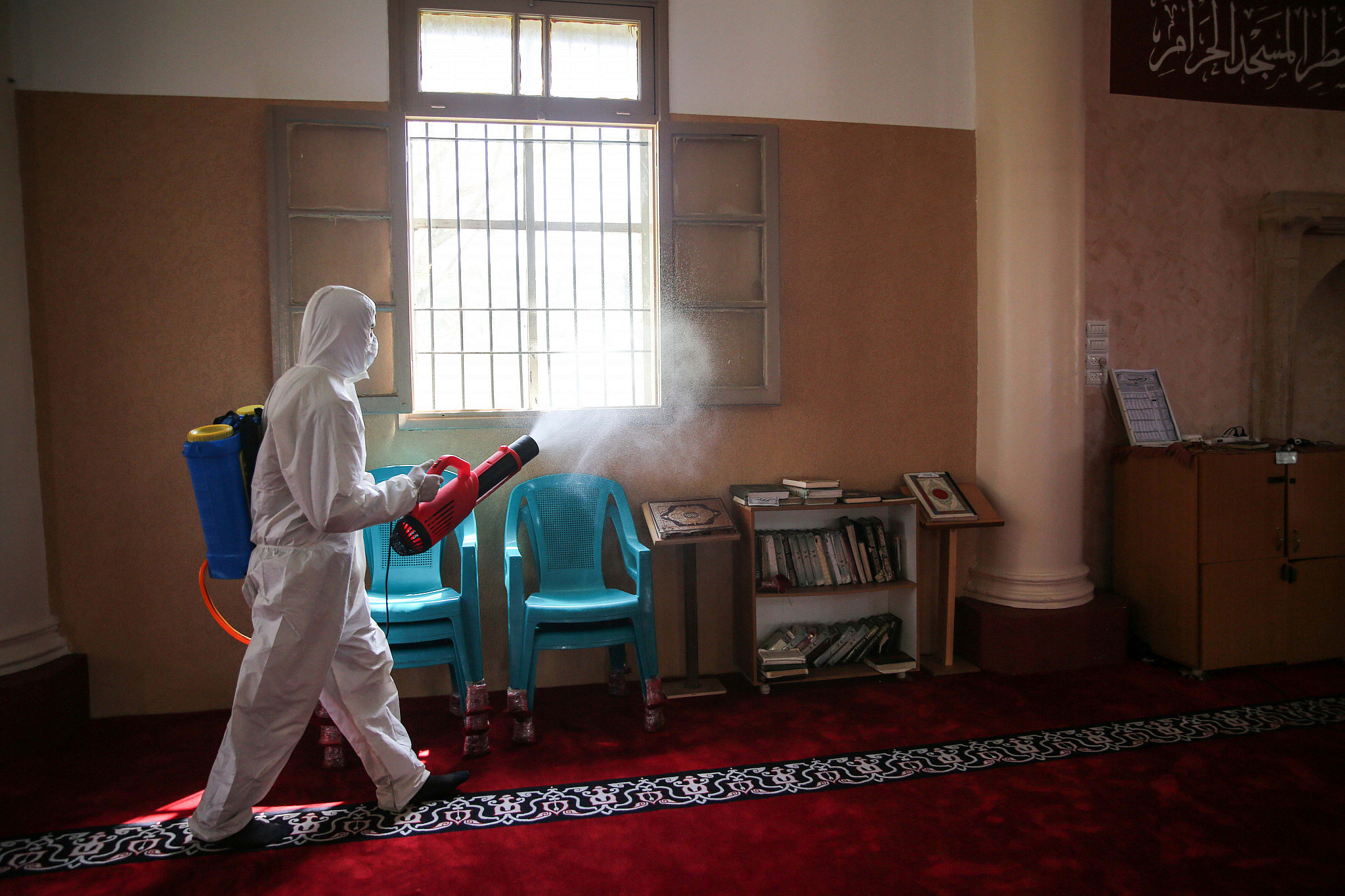 Palestinian health workers spray disinfectant as a precaution against the new coronavirus in Al-Omari Mosque in Gaza City, March 15, 2020. (Ali Ahmed/Flash90)