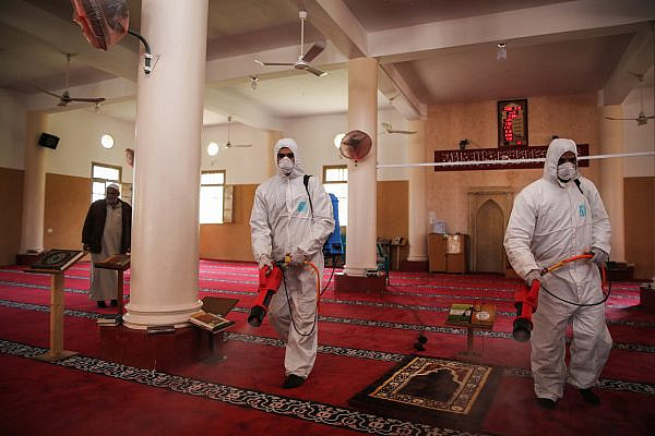 Palestinian Health workers spray disinfectant as a precaution against the new coronavirus in the Al-Omari Mosque in Gaza City. March 15, 2020. (Ail Ahmed/Flash90)