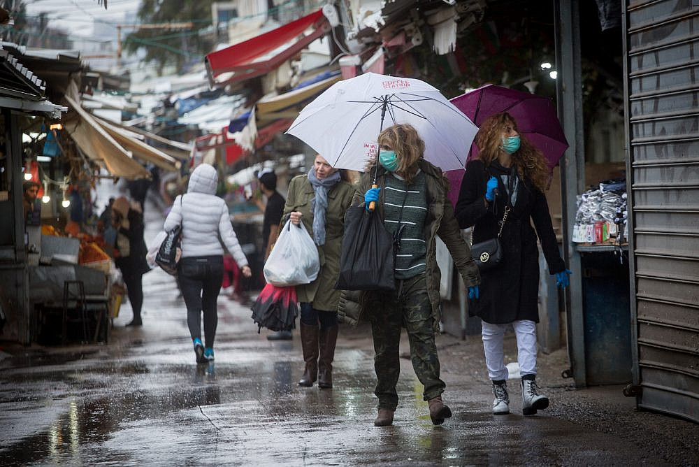 Shoppers walk through Tel Aviv's Carmel Market after the Israeli government ordered all bars, restaurants, and malls to close in an effort to contain the spread of the coronavirus. (Miriam Alster/Flash90)