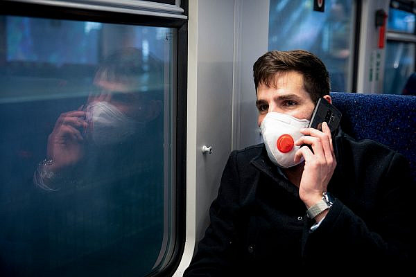 A man wears a face mask for protection from coronavirus as he takes the train to Haifa, on March 17, 2020. (Yossi Aloni/Flash90)