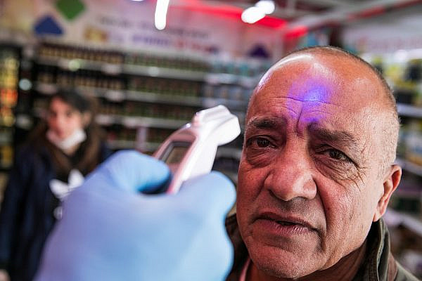 A security guard checks the temperature of customers to identify if they have fever in a Rami Levy supermarket in Jerusalem on March 18, 2020. (Olivier Fitoussi/FLASH90)