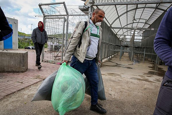 Palestinian workers from the West Bank city of Hebron carry personal belongings as they arrive to cross to Israel at a checkpoint in Tarqumiya, March 18, 2020. Photo by Wisam Hashlamoun/Flash90