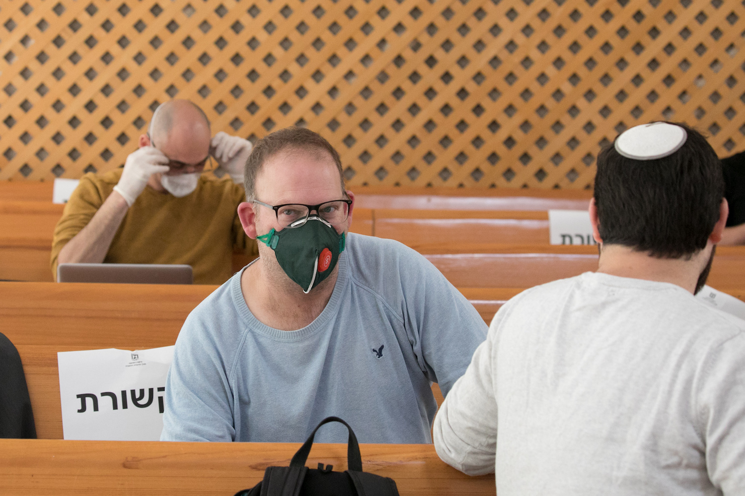 Israeli journalists wear face mask a during hearing at the High Court of Justice in Jerusalem about the decision of Israeli PM Benjamin Netanyahu to authorize the Shin Bet to monitor Israelis' cellphone location data to help combat the coronavirus, March 19, 2019. (Olivier Fitoussi/Flash90)