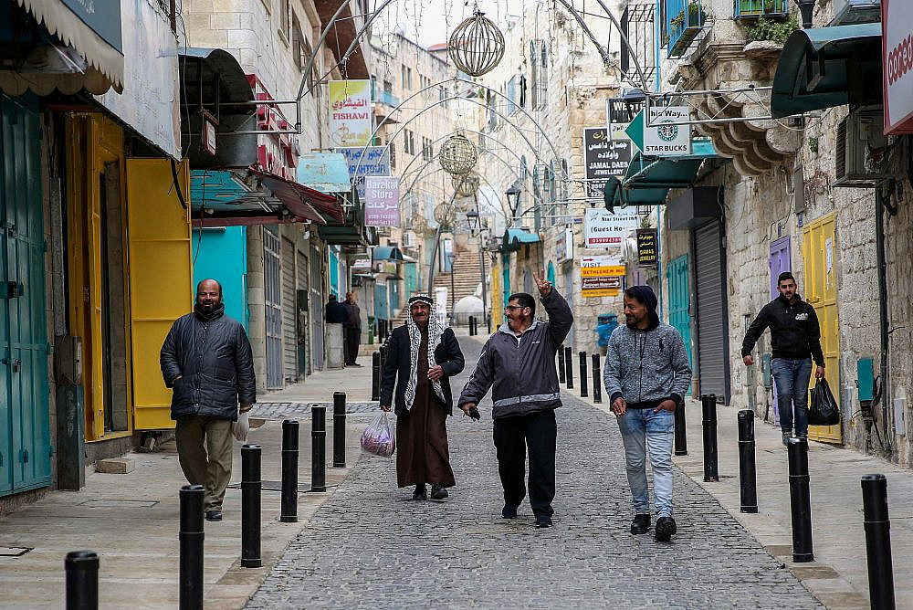 Palestinians walk on a street in the West Bank city of Bethlehem, March 19, 2020. (Wisam Hashlamoun/Flash90)