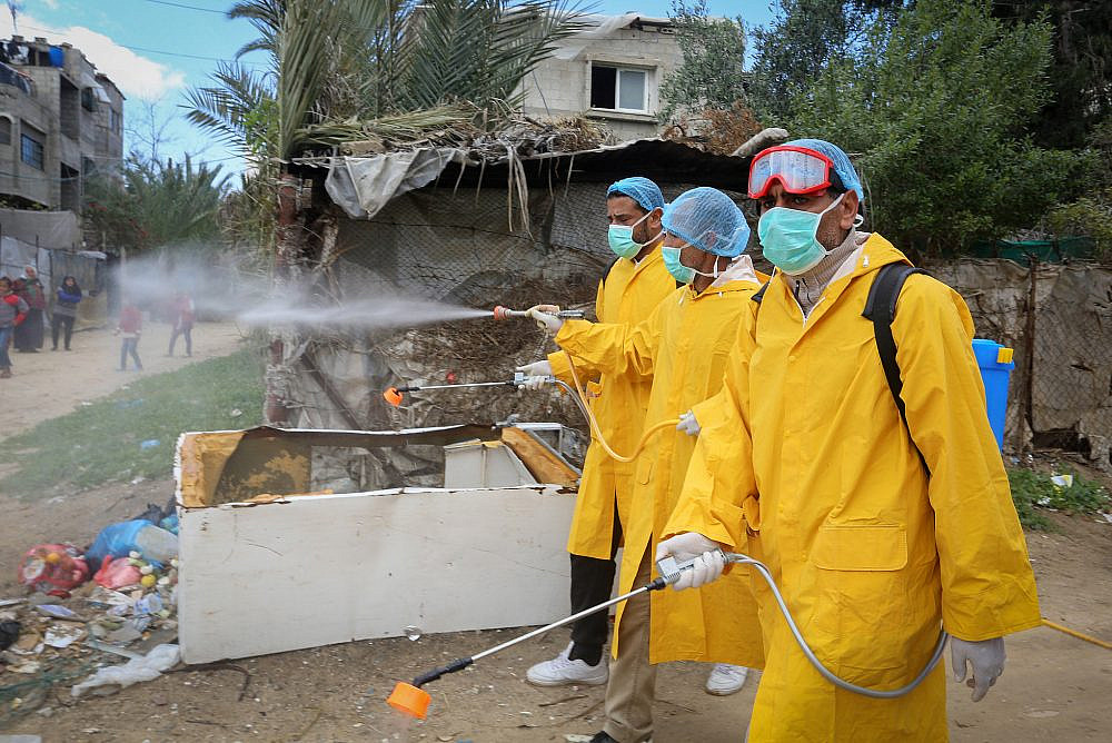 Palestinian health workers spray disinfectant as a precaution against the new coronavirus, in Rafah, southern Gaza Strip, on March 22, 2020. (Abed Rahim Khatib/Flash90)