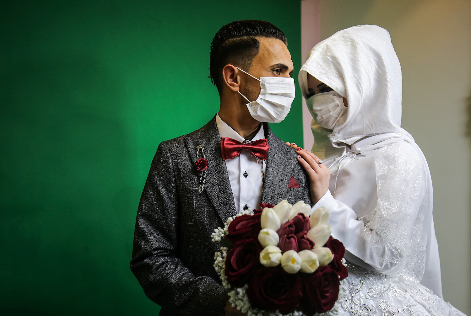 Mohamed Abu Daga and his bride Israa wear face masks during a photoshoot at a studio before their wedding ceremony in Khan Younis, Gaza Strip, on March 23, 2020. (Abed Rahim Khatib/Flash90)