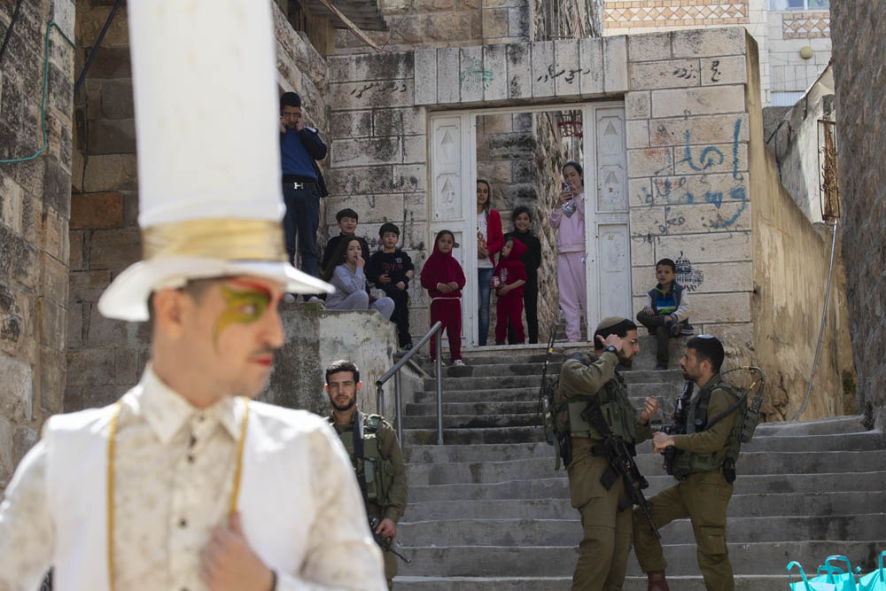 Palestinian children look on at the annual Purim parade in the city center of occupied Hebron, West Bank, March 10, 2020. Palestinians were forbidden from entering their homes for the duration of the celebration. (Oren Ziv)