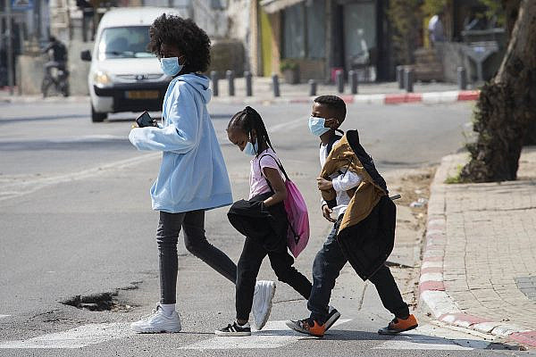 Asylum seeker children cross the street in south Tel Aviv, March 17, 2020. (Oren Ziv)
