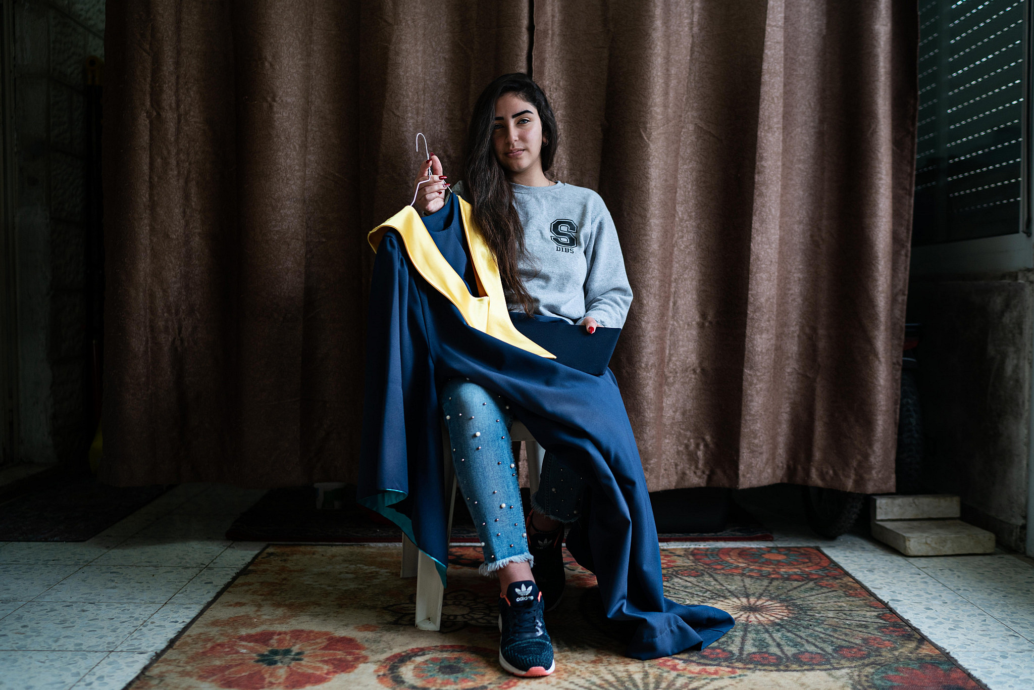 Sabaa Dibs poses with her graduation robe at her home in Bethlehem on March 12, 2020. (Samar Hazboun)