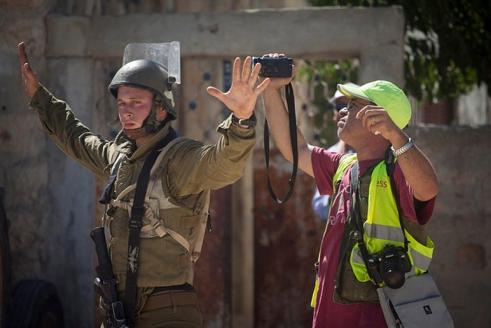 An illustrative photo of an Israeli soldier blocks a journalist from filming in the West Bank village of Nabi Saleh. (Flash90)