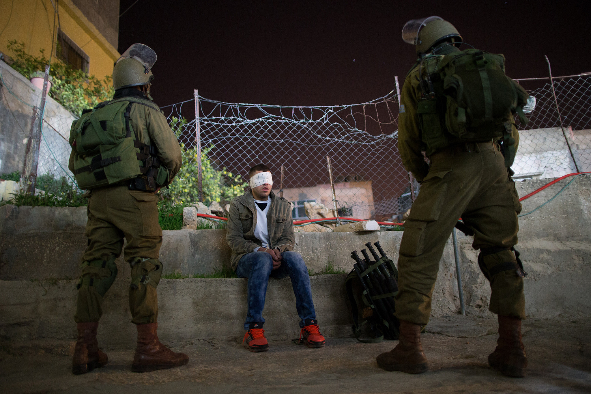 Nachshon Battalion soldiers watch over a Palestinian detainee during an operation of arresting suspects in the Dheisheh Refugee Camp, near the West Bank city of Bethlehem, on December 8, 2015. (Nati Shohat/Flash90)
