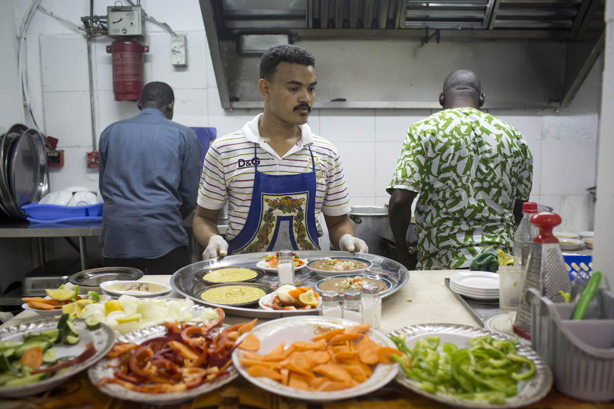 African asylum seekers work in a kitchen of a Sudanese restaurant in south Tel Aviv, May 13, 2013. (Oren Ziv)