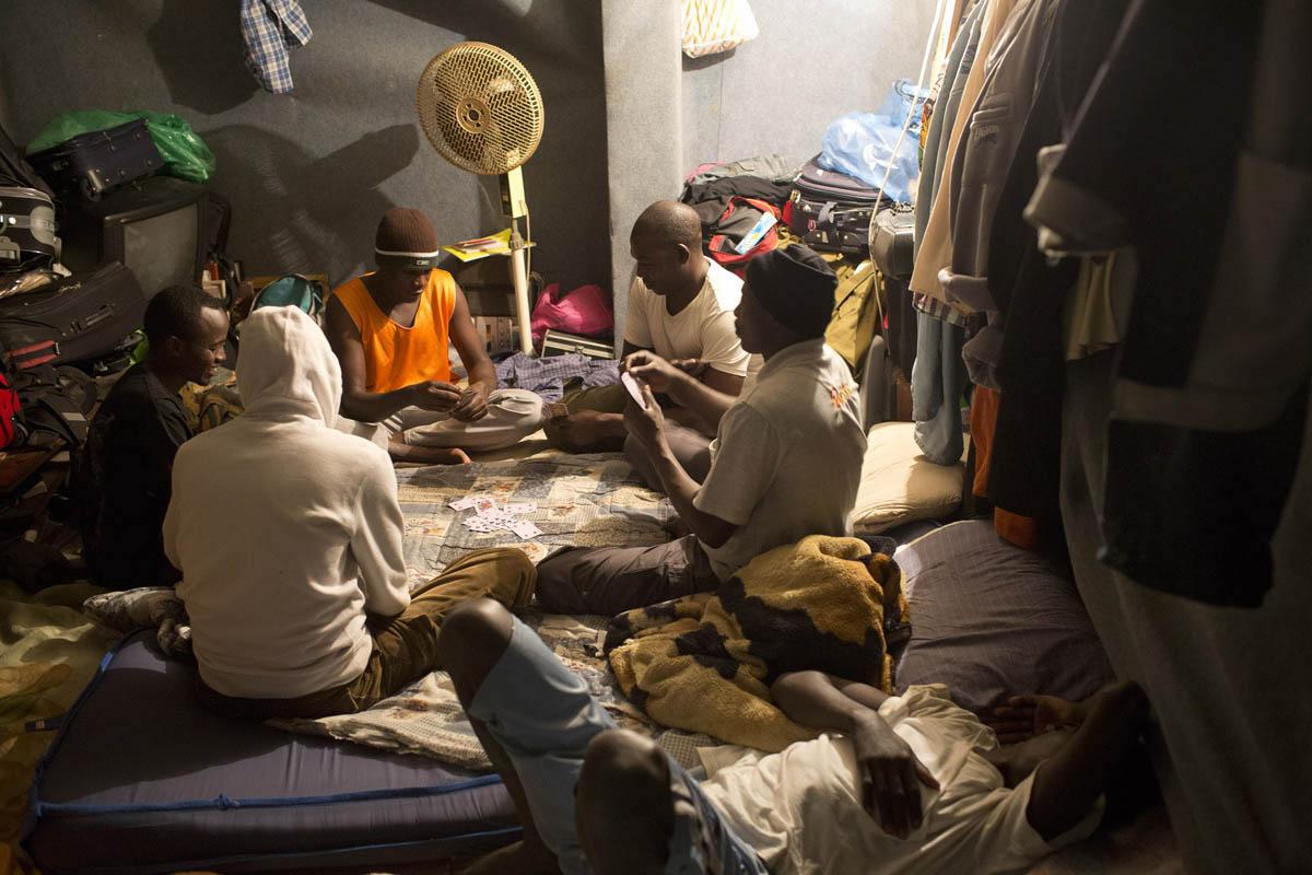 African asylum seekers play cards in an improvised shelter, south Tel Aviv, Israel, November 25, 2012. (Oren Ziv)