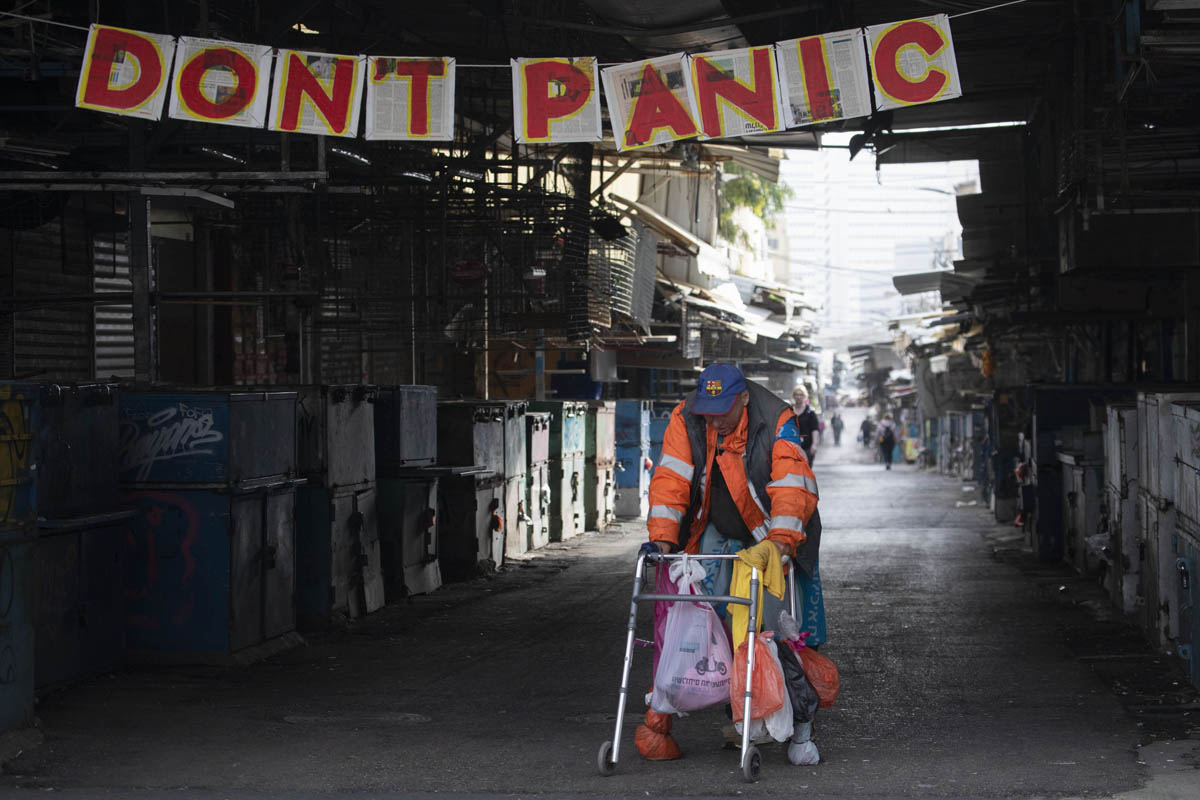 A homeless person walks past a banner that was put up by an art student at the closed Carmel Market in Tel Aviv, March 24, 2020. (Oren Ziv)