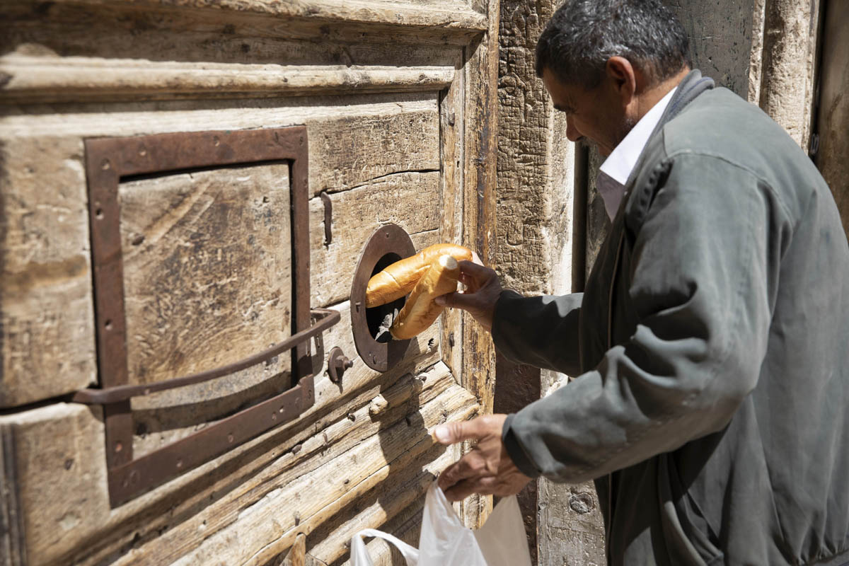 A Palestinian man brings bread to monks at the Church of the Holy Sepulchre in Jerusalem's Old City, on March 26, 2020. The church was closed to stem the spread of the coronavirus. (Oren Ziv)
