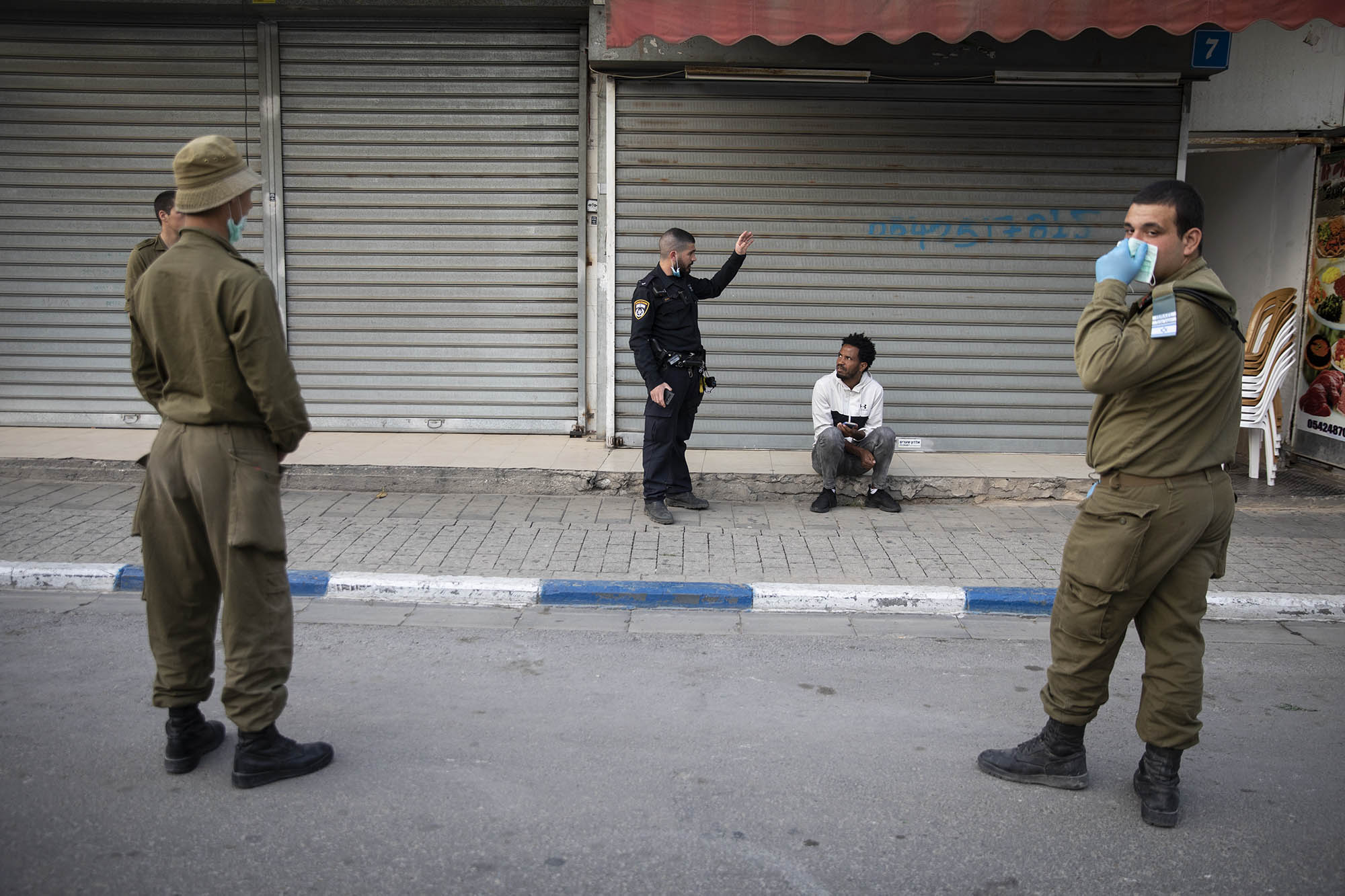 Israeli police officers and soldiers ask an asylum seeker to go inside his home in the South Tel Aviv neighborhood of Neve Shaanan, even though government regulations allow for movement in a radius of up to 100 meters away from home, March 31, 2020. (Oren Ziv)