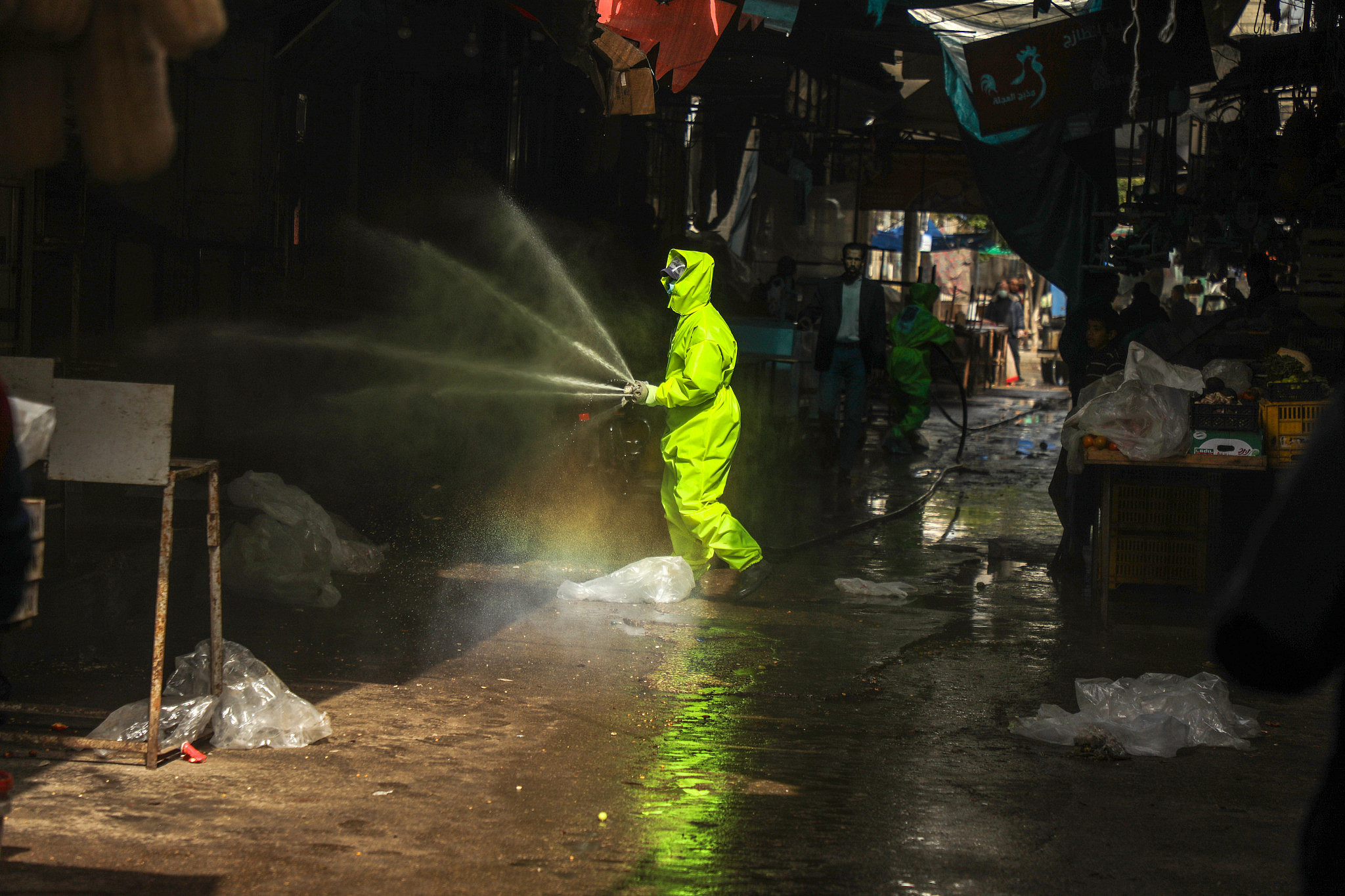 A man disinfects a street in Gaza, March 27, 2020. (Mohammed Zaanoun)