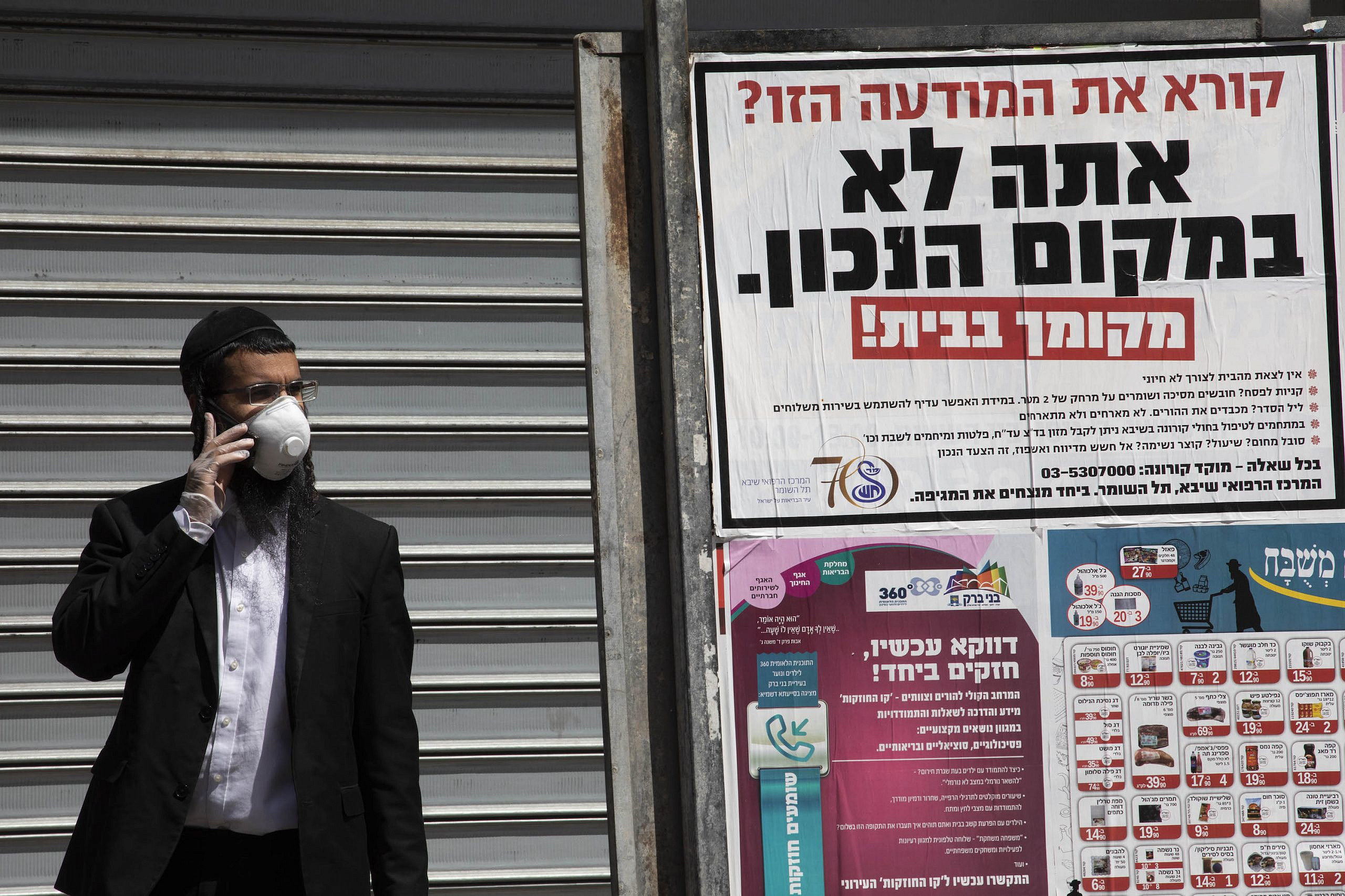 A Haredi man speaks on the phone in Bnei Brak, during a city-wide closure due to the coronavirus, April 3, 2020. (Oren Ziv)