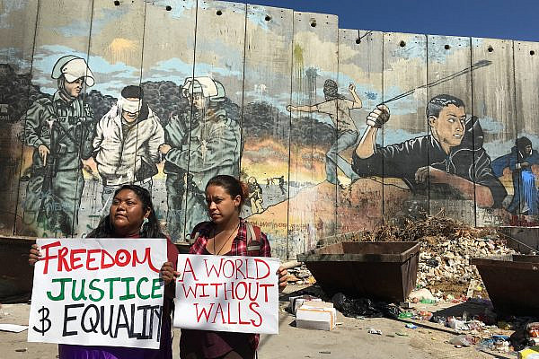 Activists with the U.S. Campaign for Palestinian Rights hold signs in front of Israel's separation wall in the West Bank. (Courtesy of USCPR)