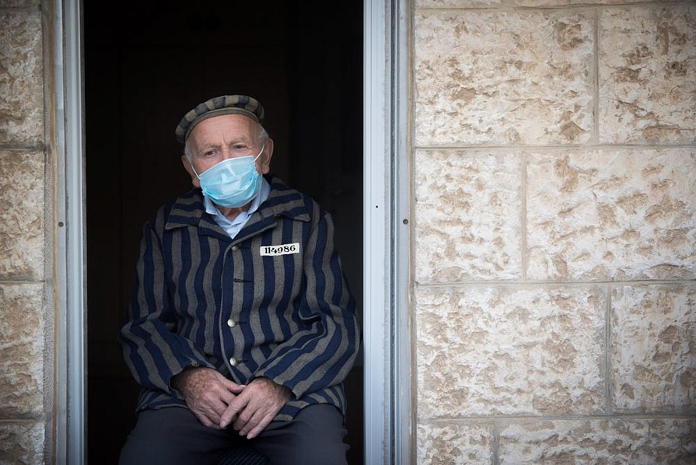A Holocaust survivor is seen wearing a face mask as he sits at his porch in Jerusalem on Holocaust Remembrance Day, April 21, 2020. (Yonatan Sindel/Flash90)