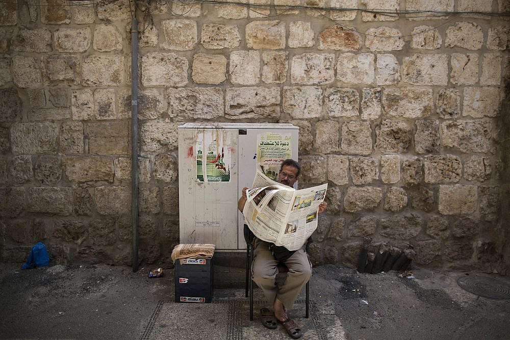 A Palestinian man reads the newspaper as he sits outside his souvenir shop in the souq, the market in Jerusalem's Old City. September 13, 2013. (Yonatan Sindel/Flash90.)