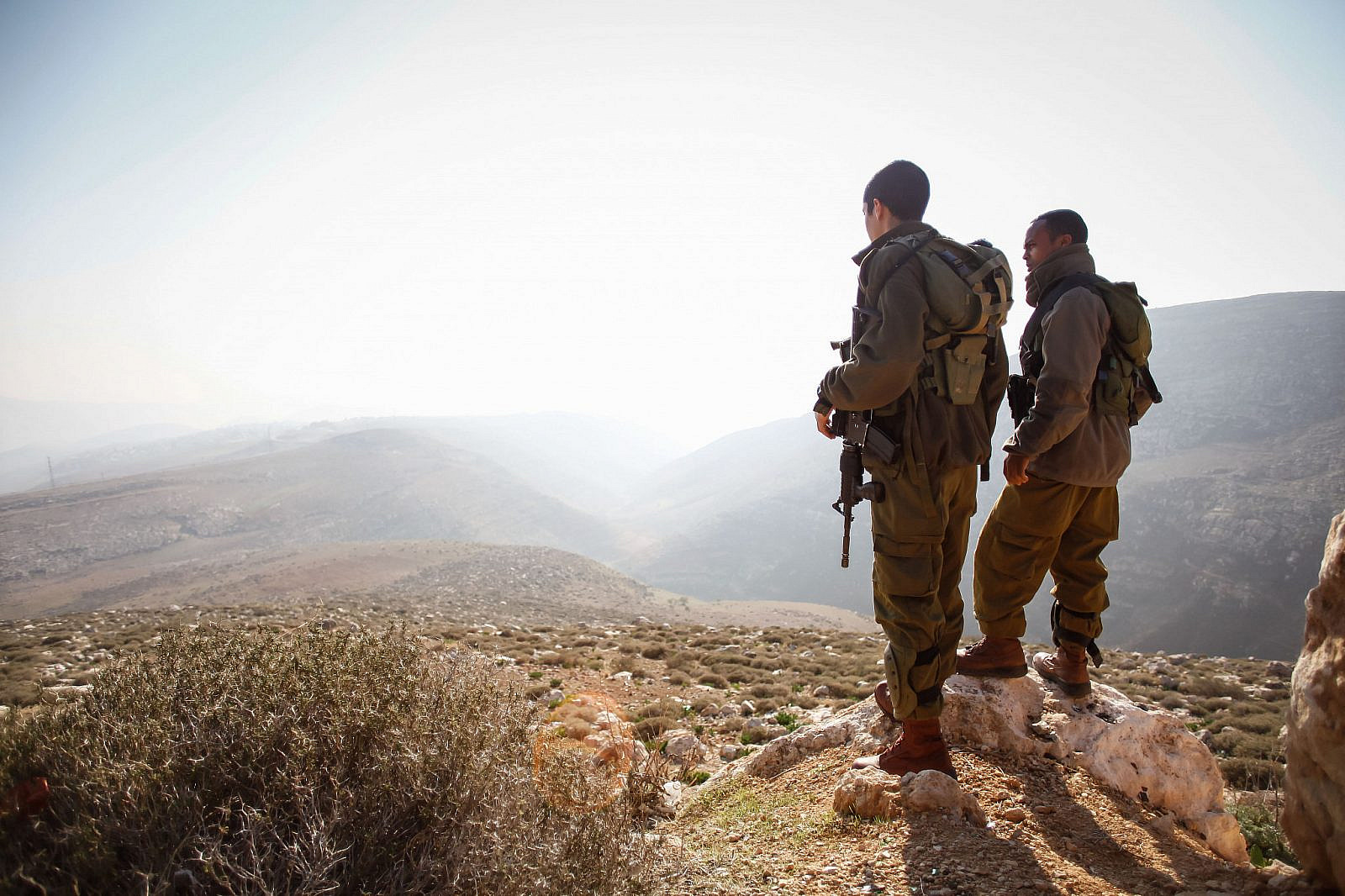 Israeli soldiers stand guard during a tour by Israeli parliament members in the Jordan Valley near the Jewish settlement of Maale Efrayim. January 2, 2014. (Uri Lenz/FLASH90)
