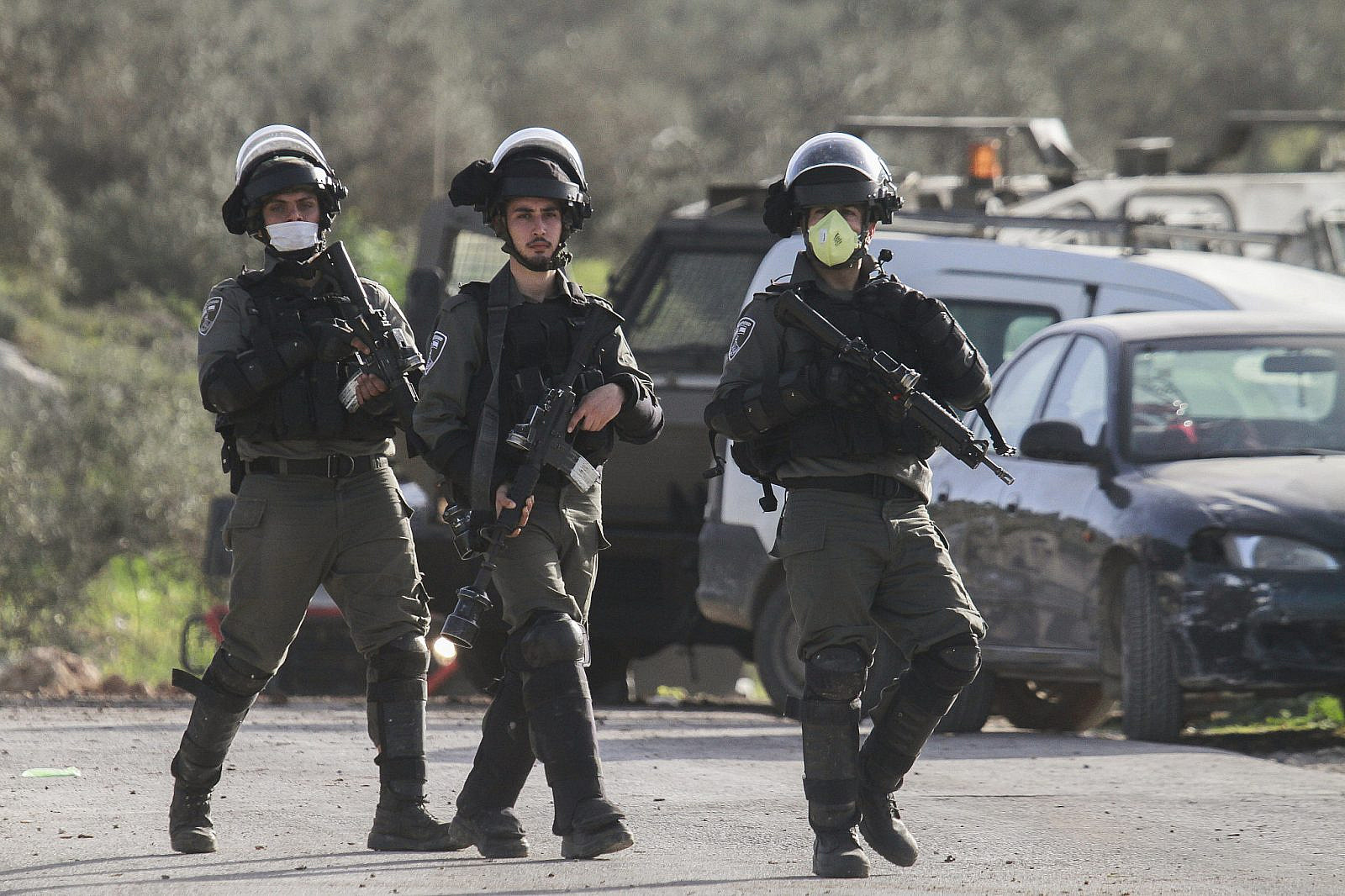 Israeli border police officers wearing face masks during clashes with Palestinian protesters at a protest against the visit of the Jewish settlers in Jabal Al-Arma, near the town of Beita in the West Bank on March 11, 2020. (Nasser Ishtayeh/Flash90)